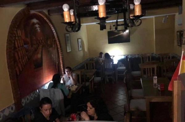 Clientes de un bar iluminándose con móviles durante los cortes de luz del fin de semana.