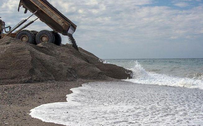 Un camión echa arena en Playa Granada mientras el agua se la lleva.
