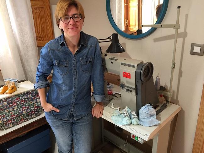 Carolina, en su estudio, ante la máquina de coser y una de sus creaciones.