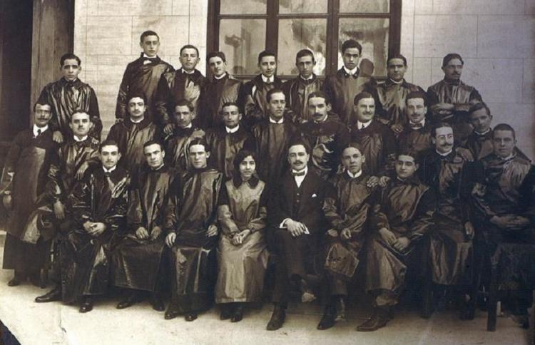 Eudoxia, en el patio de la Facultad de Medicina de C/ Rector López Argüeta. Rodeada de los alumnos de la asignatura Técnica Anatómica, 1912-3, sentada al lado del profesor José Megías Manzano.