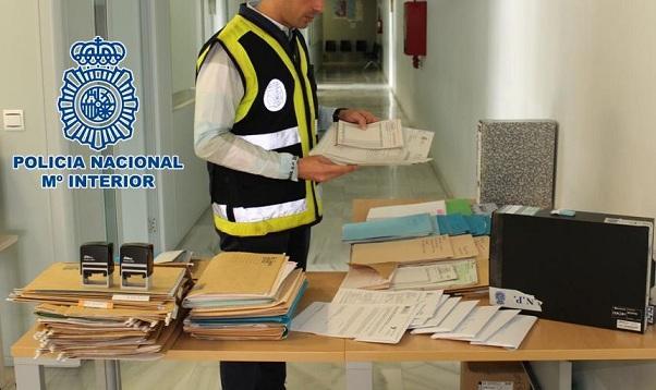 Un agente examina documentación de los detenidos.