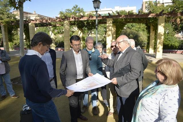 El alcalde examina los planos de la obra en la plaza.