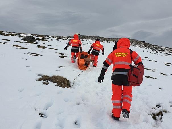 Bomberos trasladan al montañero herido.