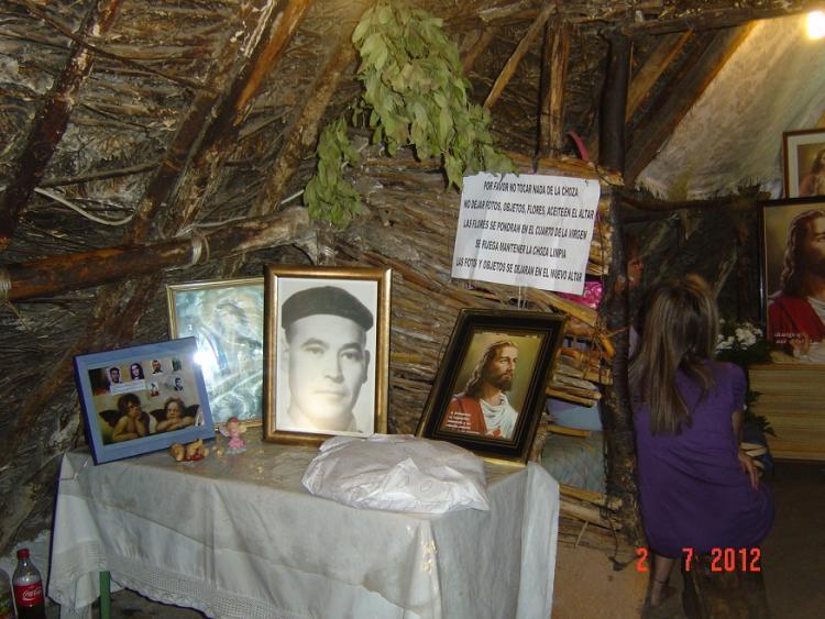 Interior de la choza, convertida en una especie de santuario, a base de fotos de santos y fotos suyas.