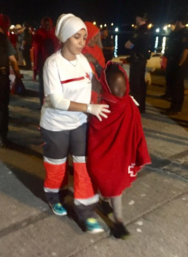 Una de los menores atendida por una voluntaria Cruz Roja.