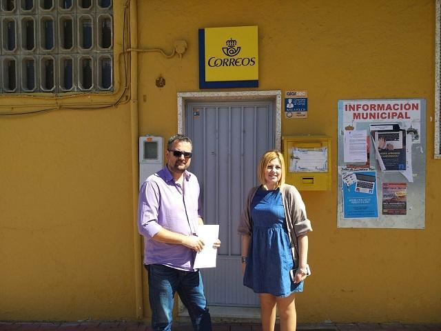 El teniente de alcalde y la concejala de Consumo, frente a una de las oficinas rurales de Correos en el municipio.