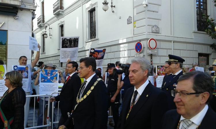 Miembros de Granada Laica muestran carteles y carocas a las autoridades.