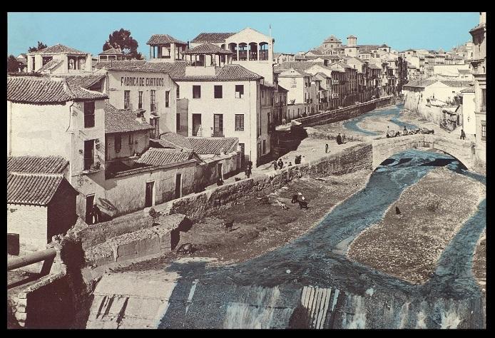 Postal coloreada del Darro descubierto en 1900; en primer término, presa de la Acequia Gorda; en el centro, el Puente de la Virgen, la parte trasera del Rastro (dcha.) y el malecón de la Acera del Darro discurriendo por la izquierda.