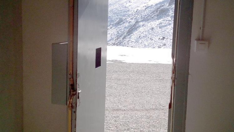 Puerta de entrada al edificio de acceso a la Cueva del Agua, reventada.