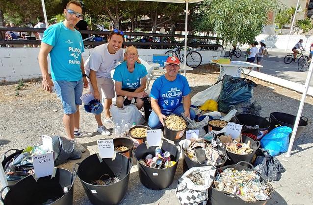 Varios voluntarios, con distintos residuos recogidos.