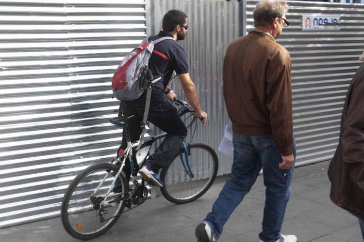 Un ciclista pasa junto a un peatón en una acera de Granada.