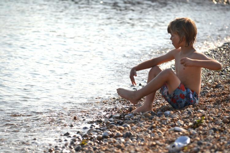 El niño se limpia los pies y no pisotea las toallas de los demás veraneantes.