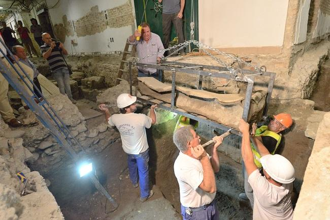 Operarios levantan el sarcófago para su traslado al Arqueológico.