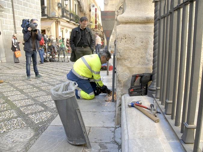 Retirada de una papelera en la calle Oficios, anclada en la pared de la Catedral