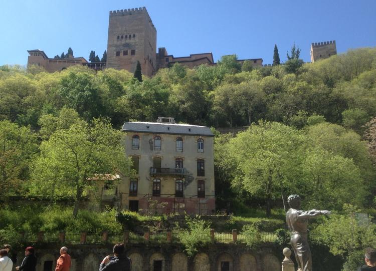 El Hotel Reúma, con la Alhambra al fondo, una estampa del Paseo de los Tristes y de Granada.