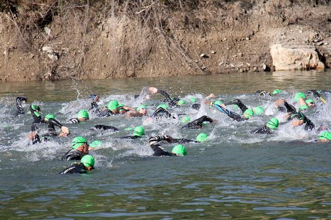 Triatletas nadando en el pantano de Canales.