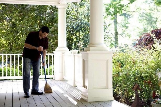 Un hombre barre el porche de su vivienda.