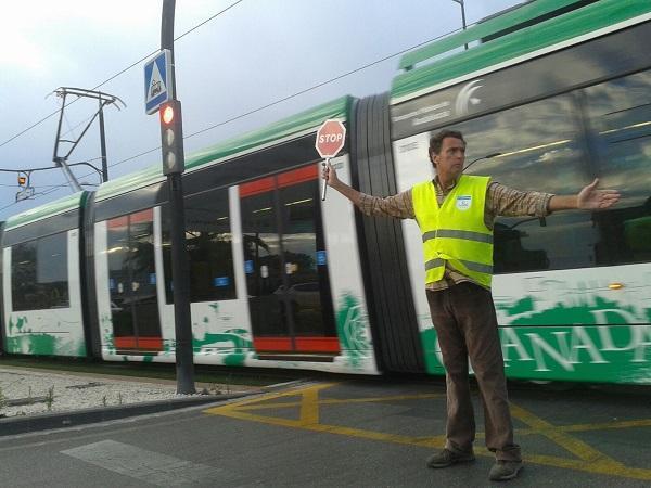 Un operario para la circulación al paso del Metro en pruebas.