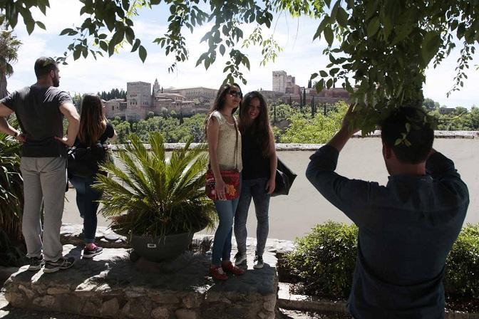 Turistas se hacen fotos con la Alhambra de fondo.
