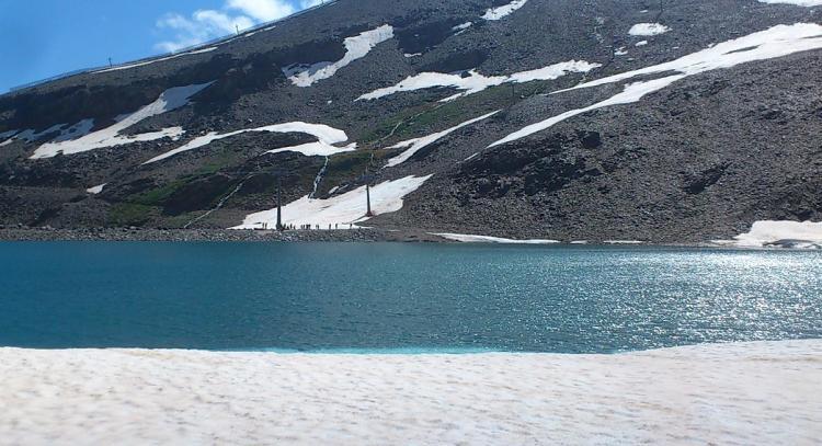 Vista de la 'playa' de nieve, con visitantes al fondo de la laguna.