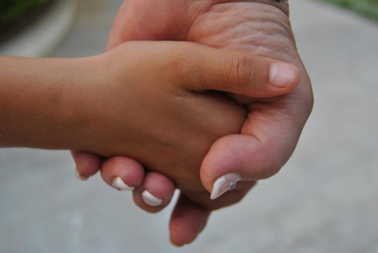 Las manos de la madre de acogida y la menor, todo un símbolo.
