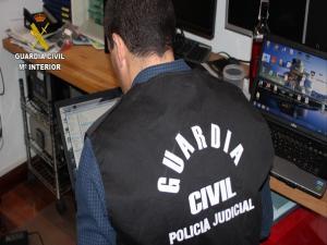 Un agente examina material informático de uno de los detenidos.