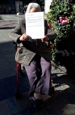 Aurora, sentada a las puertas del Ayuntamiento con el cartel en el que explica su reivindicación.