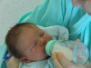 Un recién nacido toma leche de un biberón.