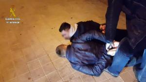Dos de los detenidos, esposados en el suelo.