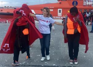 Una voluntaria de Cruz Roja atiende a dos de las personas rescatadas.