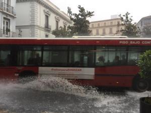 Mucha agua en Reyes Católicos al paso de un autobús urbano.