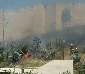 Bomberos actúan para sofocar el fuego, junto a la muralla.