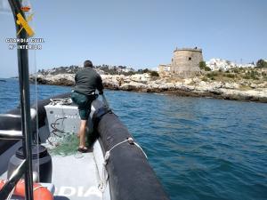 Un agente recoge el trasmallo, que medía 150 metros, junto al Tesorillo.