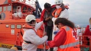 Voluntarios de Cruz Roja y miembros de Salvamento Marítimo ayudan a desembarcar a un inmigrante.