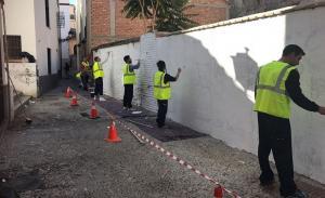 La cuadrilla limpia una pared en el Albaicín.