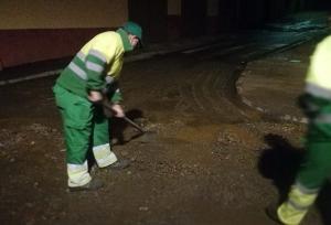 Operarios limpiando el barro en las calles de Guadix.