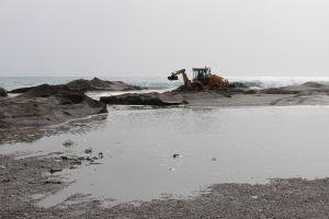 Máquina del Ayuntamiento trabajando en la salida de agua en la playa de Poniente.