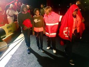 Una voluntaria de Cruz Roja atiende esta madrugada a las personas trasladadas al Puerto de Motril.