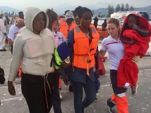 Una voluntaria de Cruz Roja atiende a la pequeña rescatada en la patera.