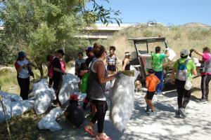 Voluntarios llevan bolsas con basura.
