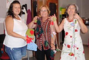 Participantes en el taller con las prendas de ganchillo.