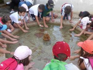 Escolares en una de las fuentes del monumento.