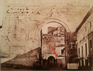 Foto anterior a 1879. Al fondo se ve la desaparecida puerta de la Alhacaba. La flecha marca donde estuvo la placa con el poema en latín.