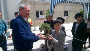 El presidente del Puerto entrega un bonsái a una de las supervivientes de Hiroshima.