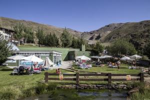 Zona de césped y piscina en el Apartahotel Trevenque.