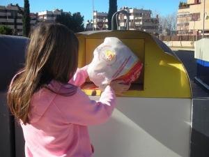 Una mujer introduce una bolsa en el contenedor de envases.