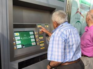 Un usuario saca su billete en la máquina expendedora.
