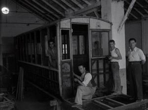 Trabajadores del taller de Puente Verde con un tranvía en proceso de recarrozado, enero de 1943.