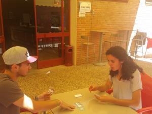 """Dos alumnos juegan a """"La Amenaza de los Sedentaris"""" en la cafetería de la facultad de Ciencias del Deporte."""