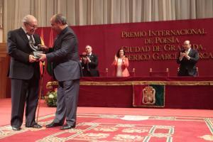 El alcalde entrega el galardón al poeta.